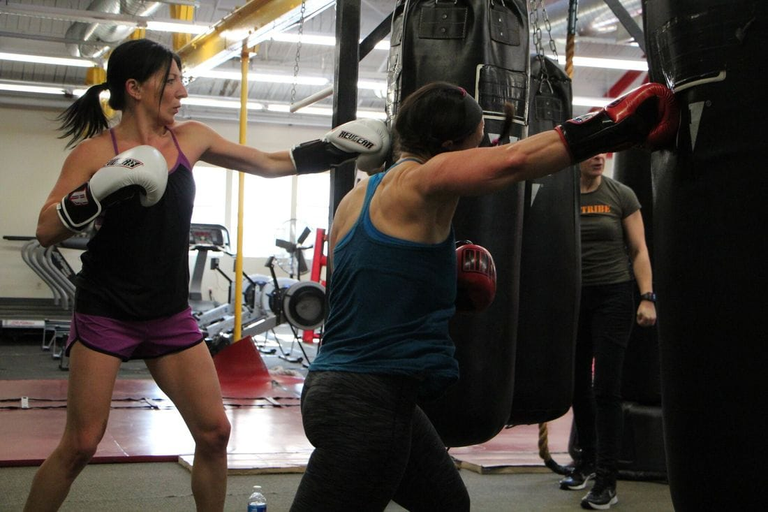 Women's boxing lesson hitting heavy bags at Bancroft Boxing and Fitness Club in Framingham Ma,